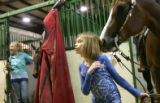 (0526) Payton Neiberger, 8, of Fort Collins, is nuzzled by her friend's horse as she holds the...