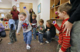 (at center) 3-year-old Logan Goodridge (cq) skips around the room as Jennifer Hancey (cq) holds...