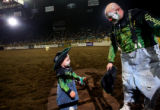 (PG11137) Rodeo clown Ryan Rodriguez, and his son, Rad, 3, leave the arena after peforming during...