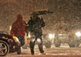 Commuters during the early morning snowfall on East Colfax Avenue at Colorado Blvd. Monday January...