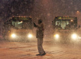 A pedestrian directs traffic around two RTD buses which spun out during the early morning snowfall...