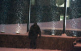 A man waits for the RTD bus during the early morning snowfall on Braodway near 16th Avenue Monday...