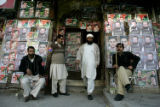RWP113 - A Pakistani man, center, leaves after casting his vote at a polling station covered with...