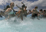 Haley Ellis, 12, cq, (left) of Centerville, SD, rushes into the Commotion Ocean atraction with...
