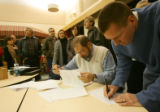 Republican voter Jeff Bull, right, of Greenwood Village, signs in while Precinct Leader Chuck...