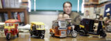 Various models of autorickshaws from around the world sit on the desk of Dr. Bryan Willson,...