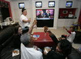 Susie Hills (cq), standing, toasts fellow debate watchers in her home in Houston, Texas, Tuesday,...