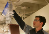 Will Medlin (cq) faculty staff at CU, pours liquid nitrogen into a cylinder, that cool samples,...