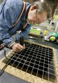 Herb Warren, mechanical tech for AVA Solar, marks samples to be cut out of a solar panel, to test...