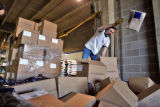 Jefferson County  Schools storage warehouse worker Doug Cone  (cq)  throws five punud bags of...