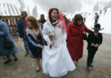 Angelina Metcalf, center,  walks with family after getting married at the 17th annual Marry Me and...