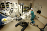 Registered nurse David Young (cq) of Englewood moves the robotic surgical unit into place before...
