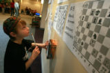 DM1860   Jonah Lawrence, 8, of Denver tries to solve some of the chess puzzles posted on the wall...