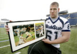 SLC107 - Utah State offensive lineman Shawn Murphy holds framed pages from Sports Illustrated...