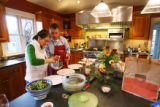 Pete Marczyk and Barbara Macfarlane make dinner at their home in Denver, with food from their...