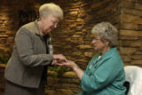 Kay Wakefield(cq) (LEFT and STANDING), chaplain, performs a blessing on the hands of Jeannette...