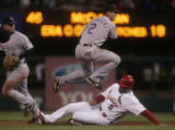 Troy Tulowitzki leaps over Albert Pujols on a double play in the 6th inning of the Colorado...