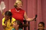 Rosedale Elementary 5th grade teacher Mrs. Sue Bryers (top in red cq) hands the microphone to...
