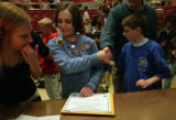 State champion Autumn Hughes shakes hands for congratulation and tries to fill out paper work at...