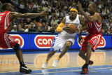 DM560 Denver's Allen Iverson drives between Houston's Carl Landry and Rafer Alston in the first...