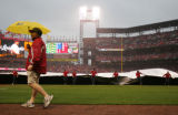 The grounds crew drags the tarp onto the field as it begins to rain for the Colorado Rockies...
