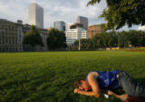 4065  Gregory Cameron, 46, lies passed out in the grass as the sun sets on Civic Center Park....