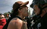 A protesters scream and confront law enforcement officers during an activist rally that marched...