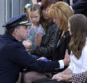 Denver Police Chief Gerry Whitman consoles Kelly Ann (Reilly) Young, flanked by her daughters,...