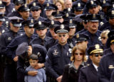 Hundreds of Denver Police Department officers stand outside the Cathedral Basilica of the...