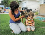 Sara Baysinger of La Salle sits with Cash, the family's 3-year-old German shepherd who was rescued...