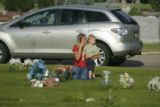 Amber Rowell and her son Aiden, 2, make a tearful visit to the gravesite of Chandler Grafner,...