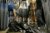 Sports Authority employees organize skis in preparation for their ski and snowboard sale called...