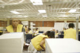 Election workers organize ballots to be counted in the mail-in ballot processing room at the...