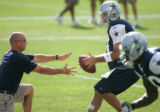 (seqn) Dallas Cowboys quarterback Tony Romo takes a snap during practice as they join the Denver...