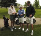 Golfer Bill Sample (cq) , left, looks at the Pace of Play Policy that marshal Chuck Nielsen (cq)...