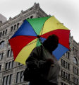 Cheryl Cain (cq) walks to work in the rain along the 16th Street Mall, Friday morning, August 15,...