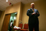 Karl Rove checks his blackberry before speaking to the Colorado Republican delegates at breakfast...