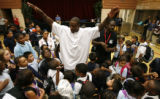 DM3526  Brandon Marshall tries to calm his young fans as they surround him and Rev. Leon Kelly...