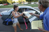 Rick Cosby, social studies teacher hands one of his flyers to student Annie Fine, a sophomore to...