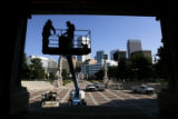 DM1666  City workers remove a ledge in the Greek Theater where pigeons like to perch as a flurry...