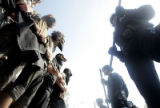 Protesters lock arms and confront law enforcement officers during a march and rally that paraded...
