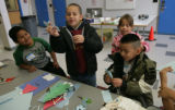 Miguel Hildago,6 laughs as Raphael Moreles, 7 makes an airplane out of his piece of paper designed...