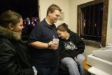Bryan Lasley, 20, (cq) comforts staff member Amy Irsik (cq) as she finishes signing a remembrance...
