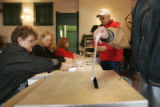 Voter Melody Meireis puts her ballot in the box after voting as her husband bruce registers in the...