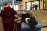 Bonfils Blood Center employee, 24 year-old Heather Teel (cq) draws blood from 74 year-old Edgar...