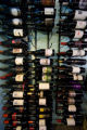 Owner of South Gaylord Wine installs metal wine racks as seen hanging on the wall in his shop when...