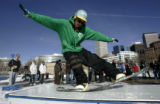 Snowboarder Pat Milbery (cq) from Denver rides a tabletop built at Civic center Park  Wednesday ...