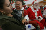 MJM212  Alma Aguilar (cq) holds her son, Dereck Aguilar, 1, as he cries after visiting Santa...