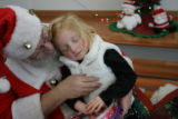 MJM421  Ava Jaksha, 3, begins to fall asleep against Santa Claus played by Richard Gibboney (cq)...