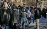 Thousands wait in a line that wrapped around the block as people line up for the annual ...